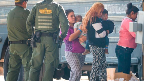 EL PASO, TEXAS - JUNE 01: Migrants are loaded onto a bus by U.S. Border Patrol agents after being detained when they crossed  into the United States from Mexico on June 01, 2019 in El Paso, Texas. The location is in an area where migrants frequently turn themselves in to Border Patrol and ask for asylum after crossing the border. In recent months, U.S. immigration officials have seen a surge in the number of asylum seekers arriving at the border.  (Photo by Joe Raedle/Getty Images)