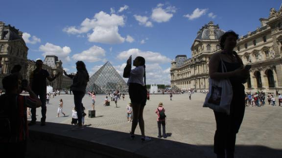 Tourists pose for the pictures at the Louvre Museum during the first Summer hot day on June 21,2019 in Paris,France. (Photo by Paulo Amorim/NurPhoto via Getty Images)