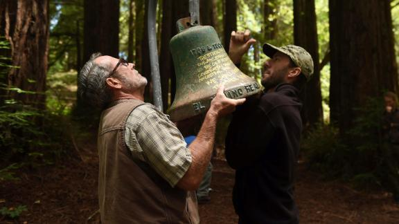 UC Santa Cruz employees David Jessen, left, and Mitch Smith remove a mission bell from campus Friday.