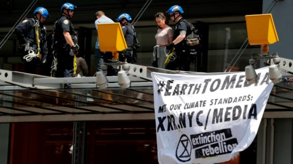New York Police officers take into custody activists who climbed on the awning of the New York Times building to hang signs during a climate change rally, Saturday, June 22, 2019, in New York.