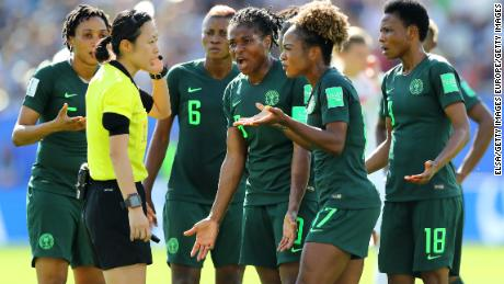 Nigeria players confront Yoshimi Yamashita after the referee awards a penalty to Germany.