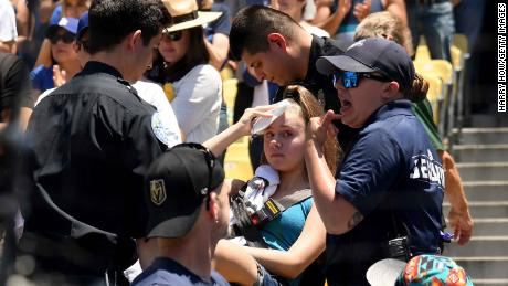 An injured fan is taken away on a stretcher after she was hit by a foul ball during the first inning of the Dodgers-Rockies game on Sunday.