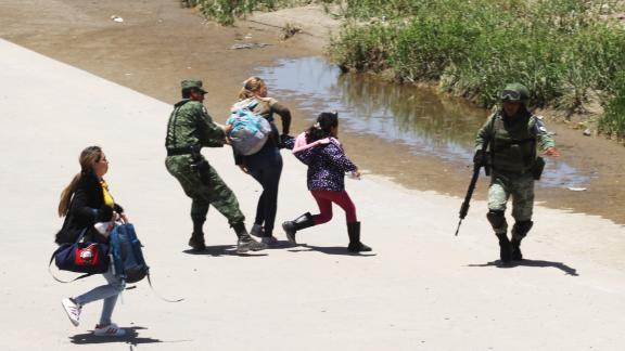 TOPSHOT - Mexican National Guard members prevent Central American migrants from crossing the Rio Bravo, in Ciudad Juarez, State of Chihuahua, on June 21, 2019. - Mexican President Andres Manuel Lopez Obrador suggested Friday he and US counterpart Donald Trump should hold their first meeting in September to review progress on the countries