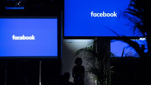 """The Facebook Inc. logo sits on screens ahead of the global launch event of """"Workplace"""" at the Facebook Inc. offices in London, U.K., on Monday, Oct. 10, 2016. Workplace is meant to help employees collaborate with one another on products, listen to their bosses speak on Facebook Live and post updates on their work in the News Feed. Photographer: Jason Alden/Bloomberg"""