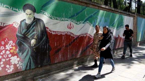 People walk past a mural painting showing the founder of the Islamic republic Ayatollah Ruhollah Khomeini and the national flag along the wall of the former US embassy in the Iranian capital Tehran on June 22, 2019. - Fear of a potential war and frustration over biting sanctions are high in Iran's capital, after a last-minute decision by the US to pull back from attacking the Islamic Republic. (Photo by ATTA KENARE / AFP)        (Photo credit should read ATTA KENARE/AFP/Getty Images)