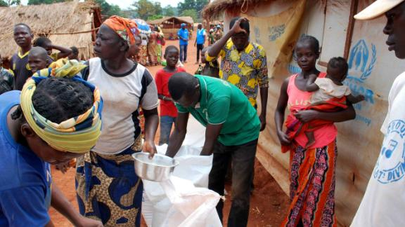 People living in the Bria camp collect rations.