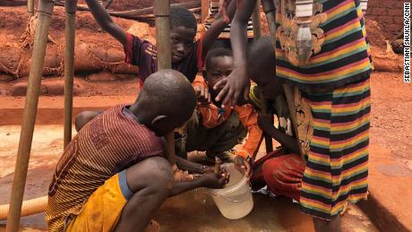Children gather water at a filling station within the camp.