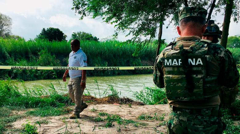 Mexican authorities walk along the Rio Grande bank where the bodies of father and child were found.
