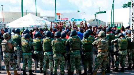 Surrounding military officers Migrants protesting in front of a dugout in Tapachula, Mexico June 18