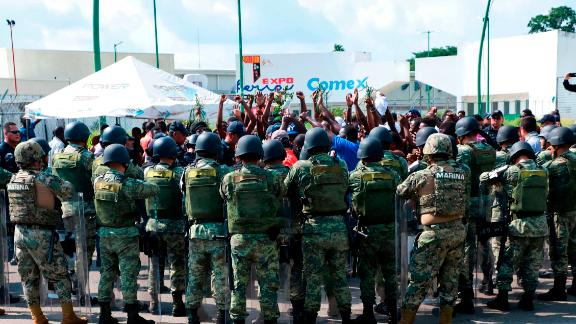Military officers surround migrants protesting outside a shelter in Tapachula, Mexico, on June 18.