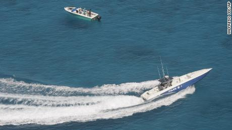 ** ADVANCE FOR WEEKEND OF APRIL 22-23 **A Royal Bahamas police speedboat, lower right, speeds in to check out a suspicious vessel near a possible drug drop zone Thursday, April 6, 2006, in the Bahamas. (AP Photo/Wilfredo Lee)