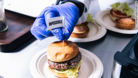 A technician places a flag toothpick into a burger with an Impossible burger patty at the test kitchen inside Impossible Foods headquarters in Redwood City, California.