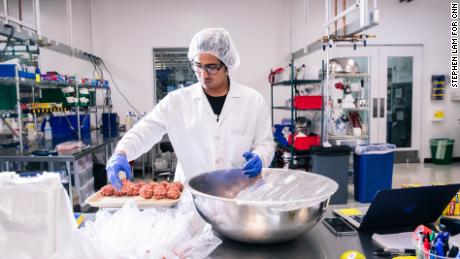 A technician weighs a tray of Impossible meatballs inside the test kitchen.