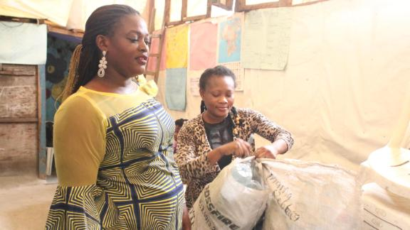Oriola Oluwaseyi (L) after delivering plastic bottles to one of her daughter