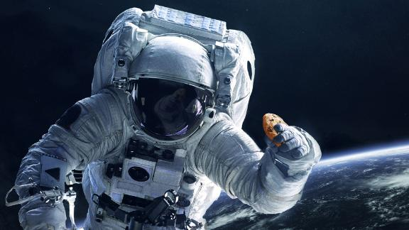 In this photo illustration provided in a press release by DoubleTree, an astronaut holds a cookie in space.