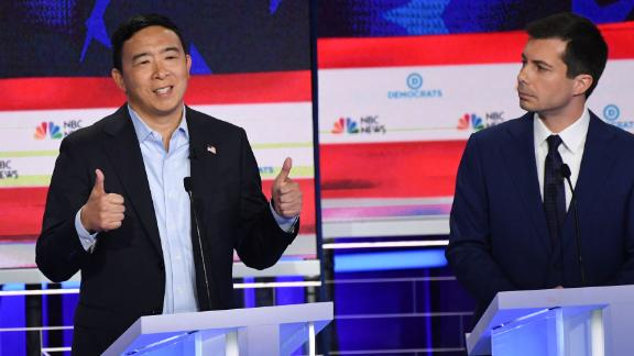 Yang answers a question while Buttigieg looks on. Yang
