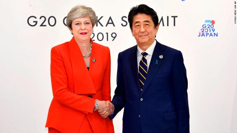Theresa May looked happier when meeting Japanese Prime Minister Shinzo Abe at the same event.