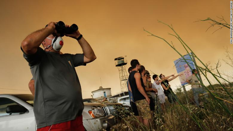 Residents gather to observe a forest fire raging near Maials in the northeastern region of Catalonia on June 27, 2019.