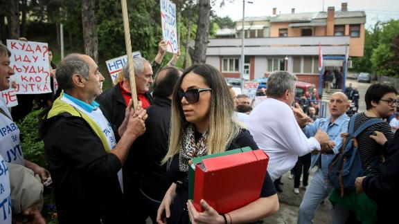 Marija Lukic (C), flanked by her lawyers, walks past supporters of Milutin Jelicic-Jutka demonstrating as she arrives at a local court to attend the trial for sexual harassment of former Mayor of Brus, Milutin Jelicic-Jutka (unseen), on May 27, 2019 in the Serbian southern town of Brus. - Marija Lukic, 31-year-old, accused her former boss, the mayor of her small Serbian town, Milutin Jelicic-Jutka, of repeated sexual assault and harassment in the workplace. Jelicic-Jutka, who has denied all accusations, resigned in March, a year after he was charged by police. (Photo by OLIVER BUNIC / AFP)        (Photo credit should read OLIVER BUNIC/AFP/Getty Images)