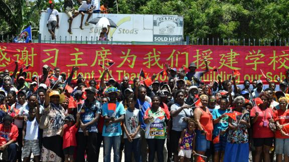 People in Papua New Guinea gather at the roadside to welcome China's President Xi Jinping in Port Moresby on November 16, 2018, ahead of the Asia-Pacific Economic Cooperation (APEC) Summit. A banner thanks Xi for building their local school.