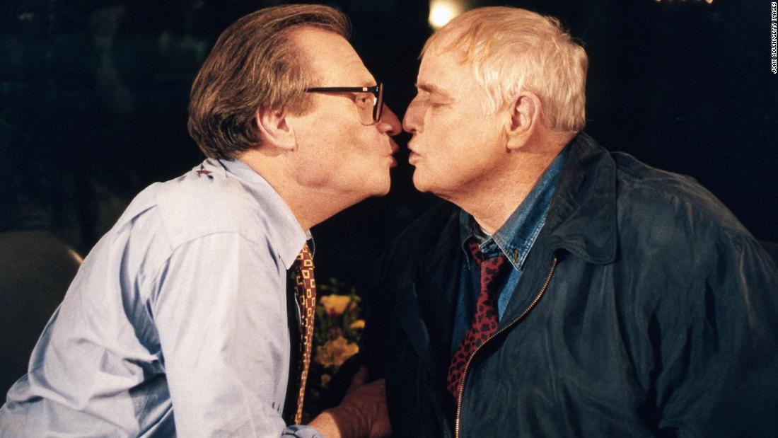 Actor Marlon Brando plants a kiss on King during an interview at Brando's home in 1994. They were singing a song together.