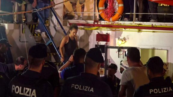 An image grab taken from a video released by Local Team on June 29, 2019, shows the Sea-Watch 3 charity ship's German captain Carola Rackete being arrested by Italian police, in the Italian port of Lampedusa, Sicily. - The Sea-Watch 3 charity ship carrying dozens of migrants rescued off Libya forced its way into the Italian port of Lampedusa on June 28 night after a lengthy standoff, the charity said. The boat's German captain Carola Rackete, 31, was arrested and the 40 migrants were still on board after the vessel docked. After manoeuvring the ship into port without permission, Rackete was arrested by police for refusing to obey a military vessel, a crime punishable by between three and 10 years in jail. She offered no resistance and was escorted off the vessel without  handcuffs. (Photo by Anaelle LE BOUEDEC / various sources / AFP) / Italy OUT        (Photo credit should read ANAELLE LE BOUEDEC/AFP/Getty Images)