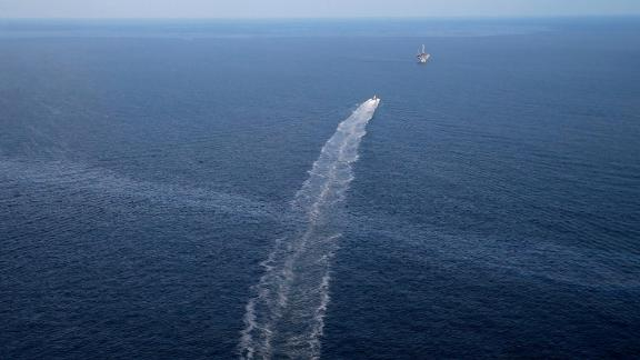 In this March 31, 2015, aerial photo, the wake of a supply vessel heading toward a working platform crosses over an oil sheen drifting from the site of the former Taylor Energy oil rig in the Gulf of Mexico, off Louisiana.