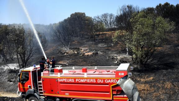 Firefighters put out hot spots on Saturday after a brushfire hit the south on France.