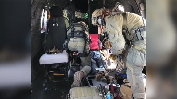 Rescuers treat a hiker who was being airlifted to a hospital.
