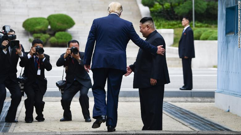 US President Donald Trump steps into the northern side of the Military Demarcation Line that divides North and South Korea as North Korea's leader Kim Jong Un looks on.