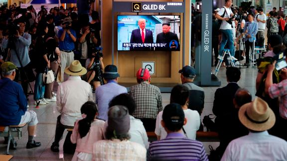 People at the Seoul Railway Station watch a news program on a TV screen showing Trump and Kim at the border village of Panmunjom on June 30.