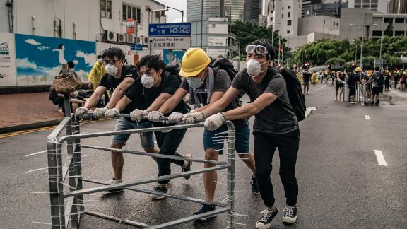 Anti-extradition protesters move barricades on a street outside the Legislative Council Complex ahead of the annual flag raising ceremony of 22nd anniversary of the city