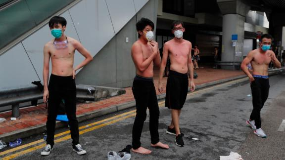 Protesters remove their shirts and try to wash their bodies after being pepper sprayed by police during protests  Monday.