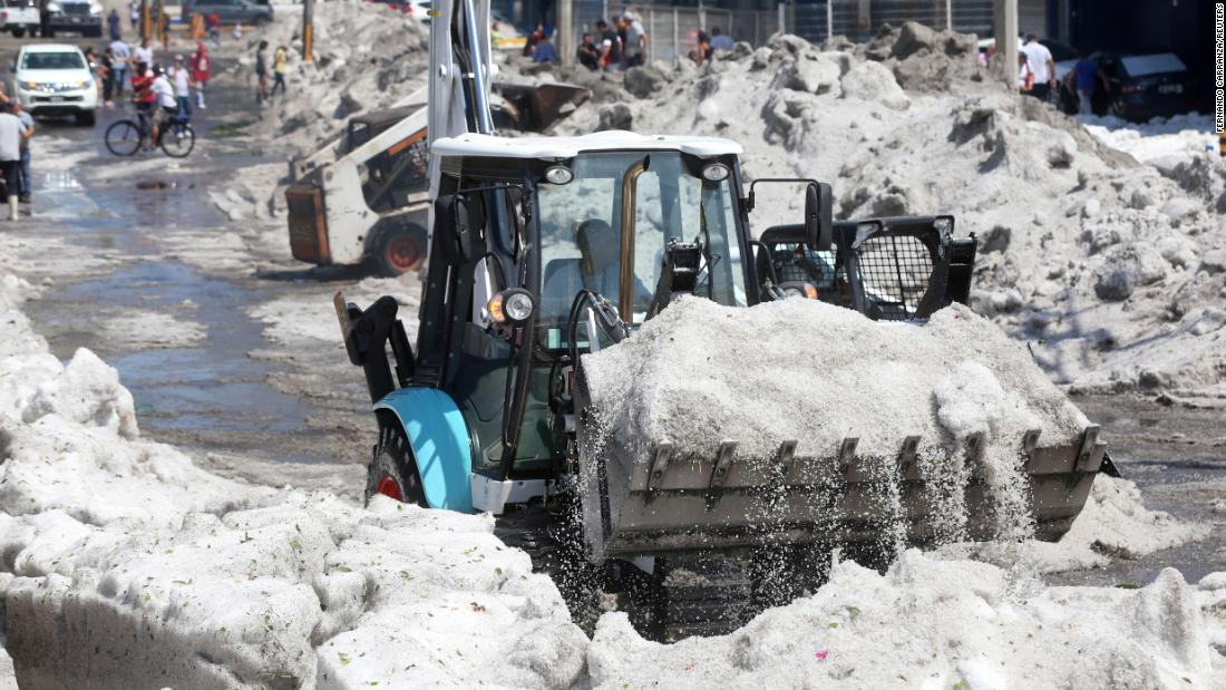 A truck carries away ice as it cleans a street.