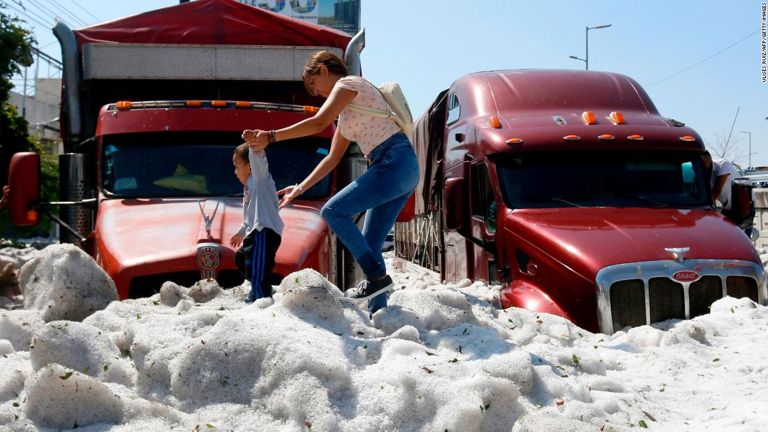 A woman and a child walk on ice in the eastern area of Guadalajara, Mexico, on Sunday, June 30. The accumulation buried some vehicles and damaged homes.