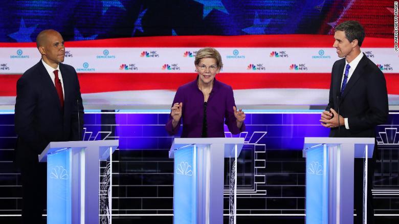 Senator Elizabeth Warren (D-MA) speaks as Senator Cory Booker (L) (D-NJ) and former Texas congressman Beto O'Rourke look on during the first night of the Democratic presidential debate.