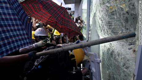 Protesters attempt to break a window at the government headquarters in Hong Kong on July 1.