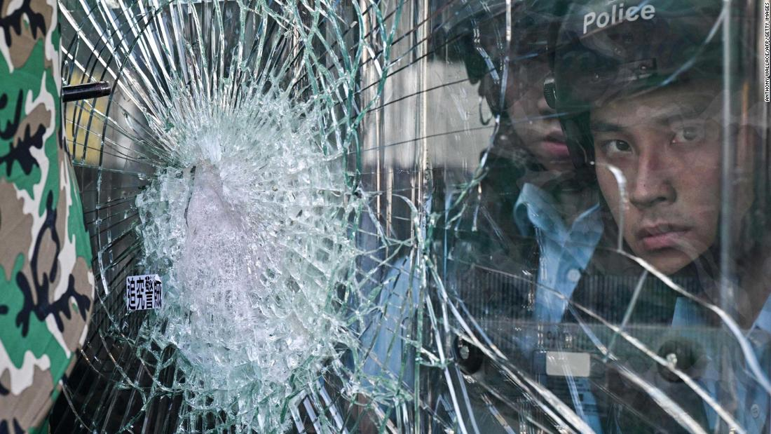 Police standing inside the Hong Kong government headquarters look through broken glass as protesters try to smash their way into the building on July 1.