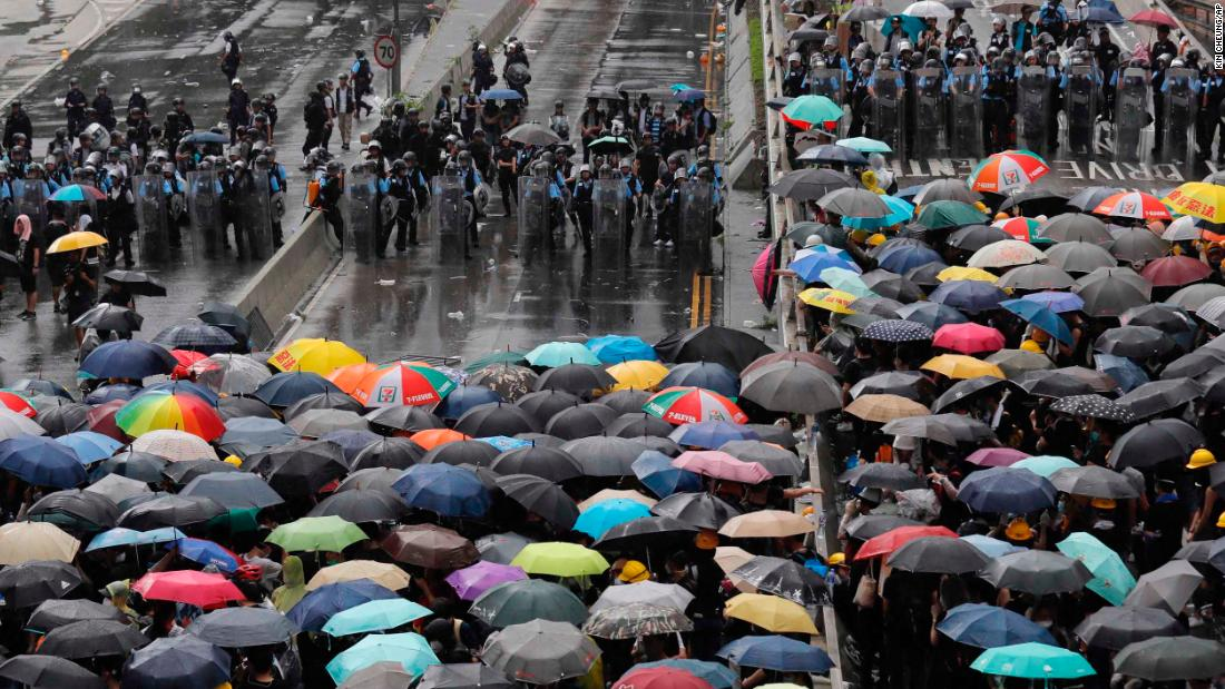 Protesters holding umbrellas face off with police officers wearing anti-riot gear on July 1.