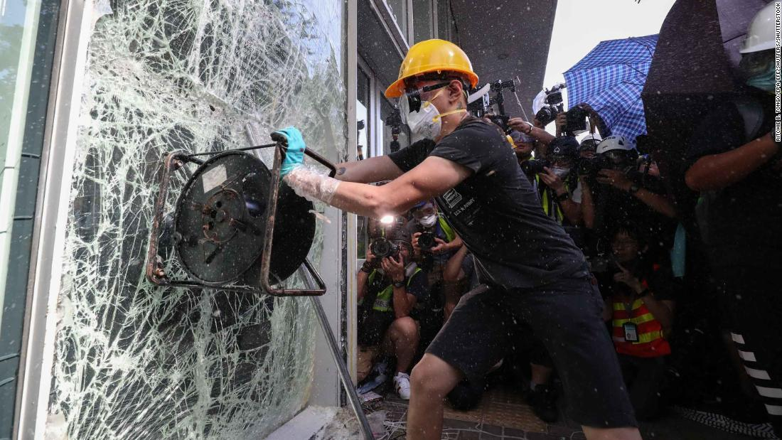 A protester smashes a window of the Legislative Council building.