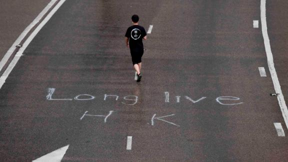 "A protester wearing a T-shirt with the word ""revolution"" walks past an inscription on a road that reads ""Long Live HK."""
