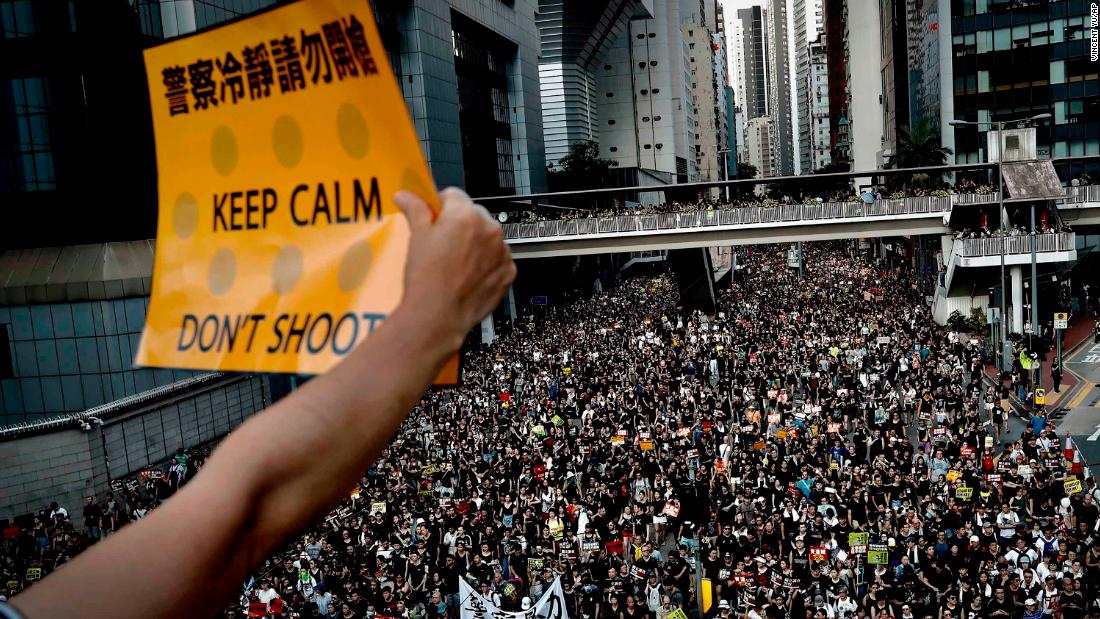 A protester holds up a placard as thousands flood the streets of Hong Kong on July 1.