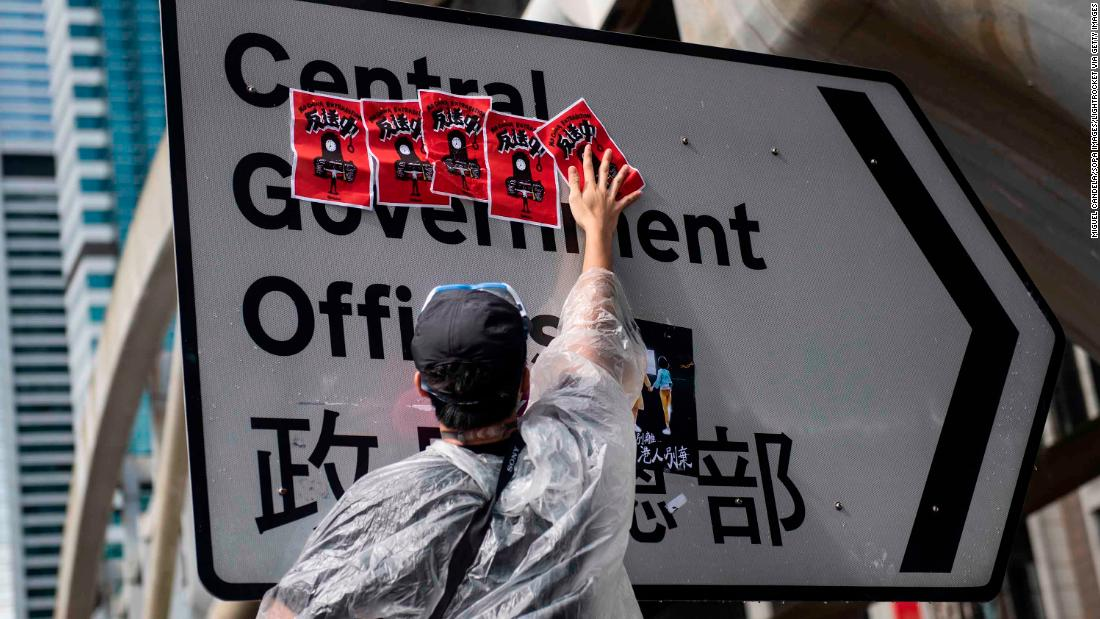 A protester places anti-government posters at the traffic sign that indicates the entrance to the government complex building.