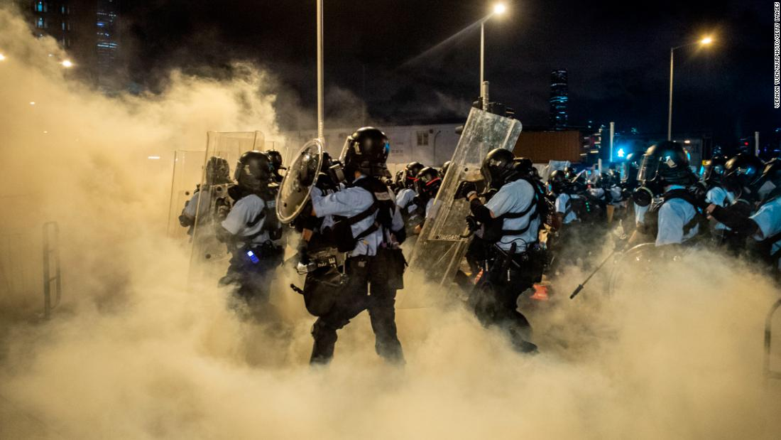 Police officers walk through tear gas as they break up the crowd.