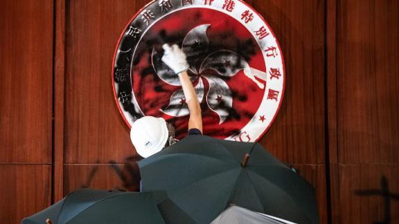 A protester defaces the Hong Kong emblem after protesters broke into the government headquarters in Hong Kong on July 1, 2019, on the 22nd anniversary of the city's handover from Britain to China.