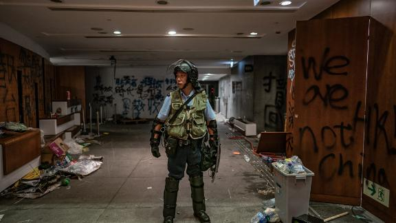 HONG KONG - JULY 2: A riot police stands near graffiti inside the Legislative Council building after it was damaged by demonstrators during a protest on July 2, 2019 in Hong Kong, China. housands of pro-democracy protesters faced off with riot police on Monday during the 22nd anniversary of Hong Kong's return to Chinese rule as riot police officers used batons and pepper spray to push back demonstrators. The city's embattled leader Carrie Lam watched a flag-raising ceremony on a video display from inside a convention centre, citing bad weather, as water-filled barricades were set up around the exhibition centre. (Photo by Anthony Kwan/Getty Images)