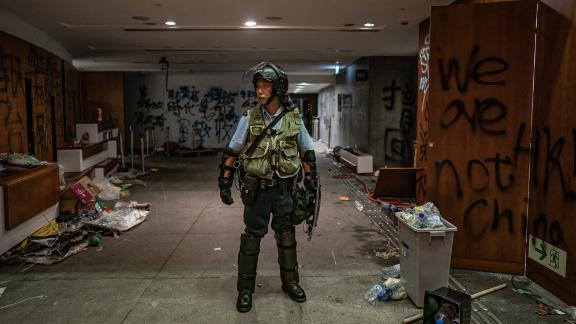 HONG KONG - JULY 2: A riot police stands near graffiti inside the Legislative Council building after it was damaged by demonstrators during a protest on July 2, 2019 in Hong Kong, China. housands of pro-democracy protesters faced off with riot police on Monday during the 22nd anniversary of Hong Kong