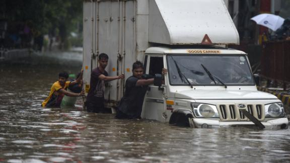 Indian men push a truck along a flooded street after heavy rain showers in Mumbai on July 1, 2019. - Heavy rains flooded parts of India's financial capital of Mumbai on July 1 as the country's four-month summer monsoon swung into full force. (Photo by PUNIT PARANJPE / AFP)        (Photo credit should read PUNIT PARANJPE/AFP/Getty Images)