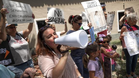 epa07690389 Irene Martinez (L) shouts slogans next to few Immigration activists to demand the end of the migrant detention centers in the US, in front of Senator Marco Rubio