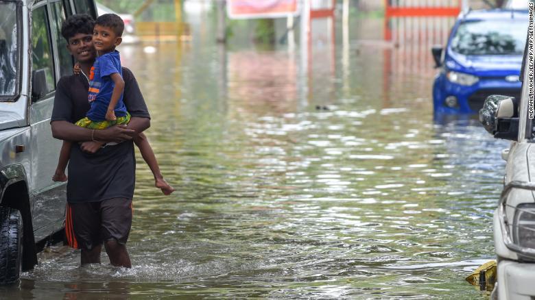 Indian residents walk along a waterlogged street on Tuesday following heavy monsoon rains in Mumbai.